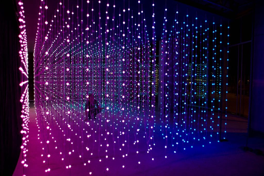 Woman walks through light installation by Squid Soup.