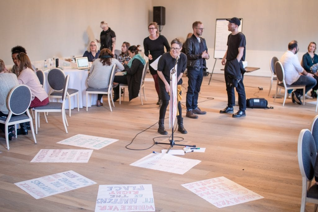 Woman stands in the centre of room. Hand-drawn posters are on the floor around her.