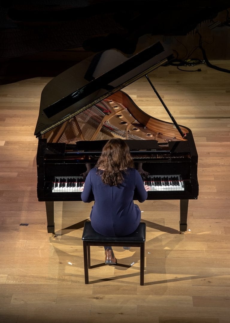 View from above as Ellie Ripley plays grand piano.