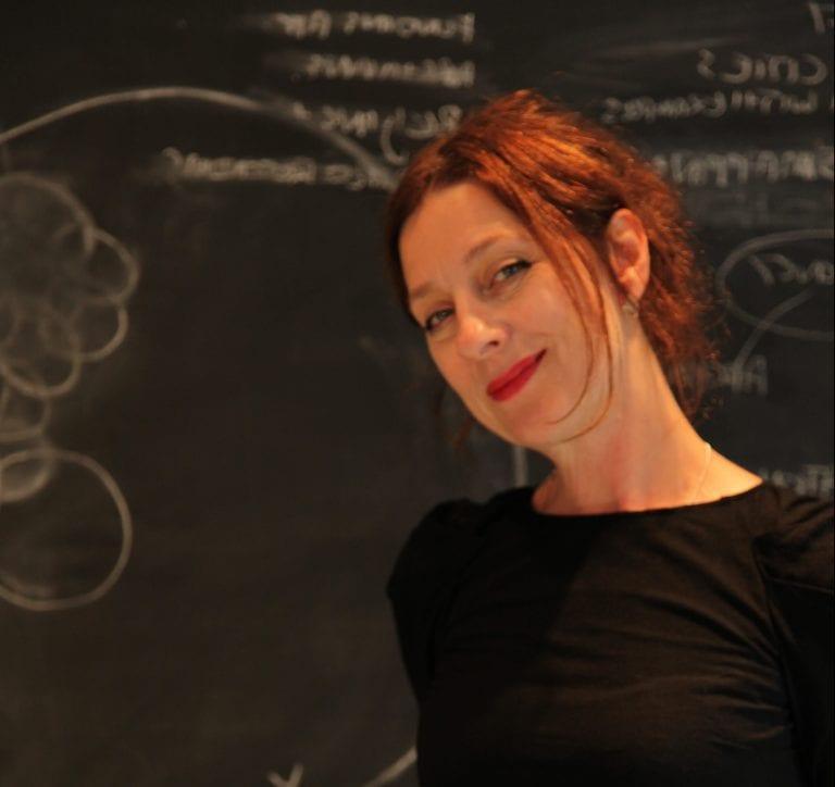 Jane Grant stands in front of blackboard.