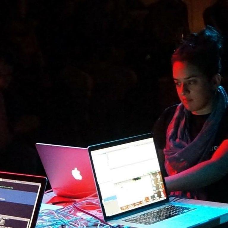 Norah Lorway working on macbook at desk.