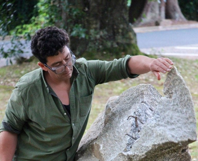 Man in glasses looks at rock spit in half.