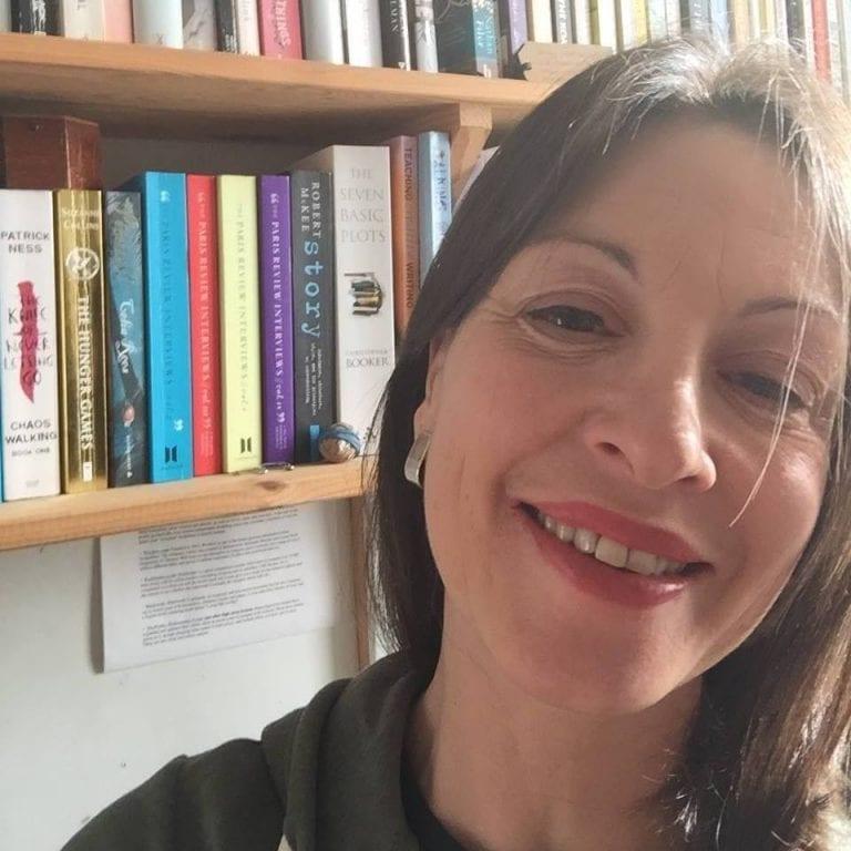 Melissa Blackburn smiles at camera with bookshelves behind her.