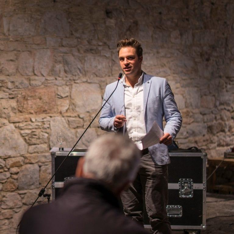 Tom Edie speaks into microphone.