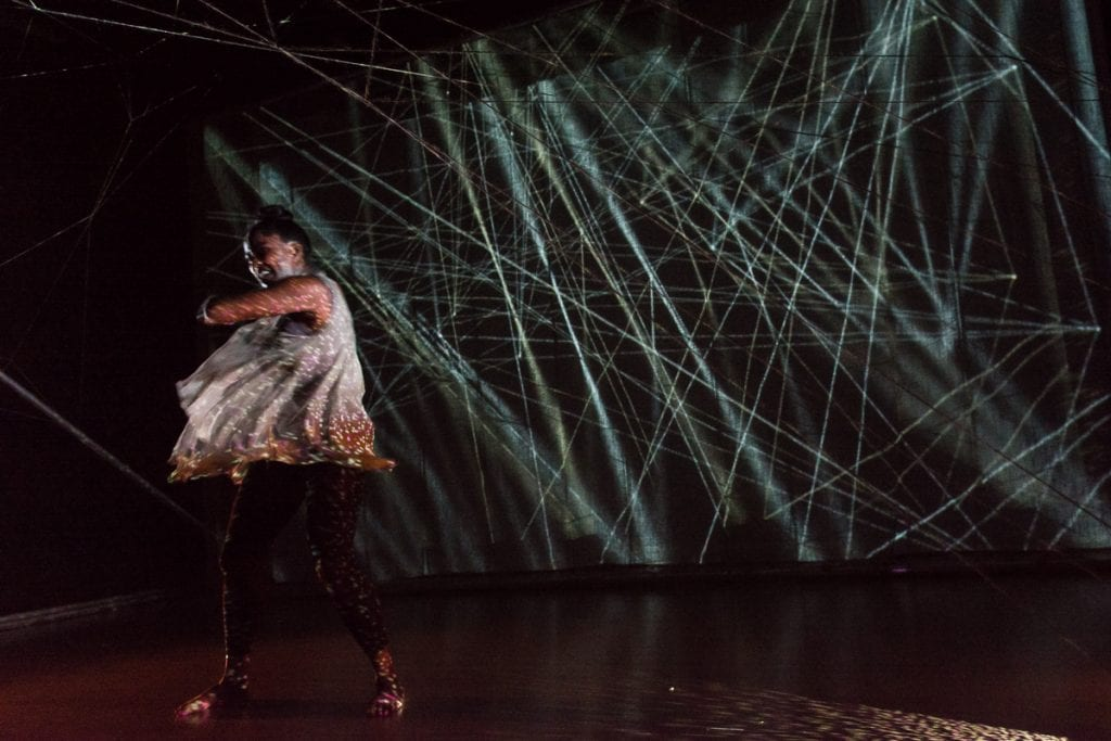 Woman dancing in front of lasers.
