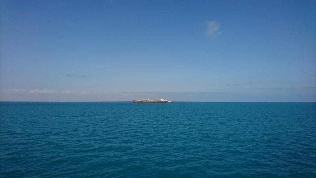Wide blue ocean with long boat in distance.