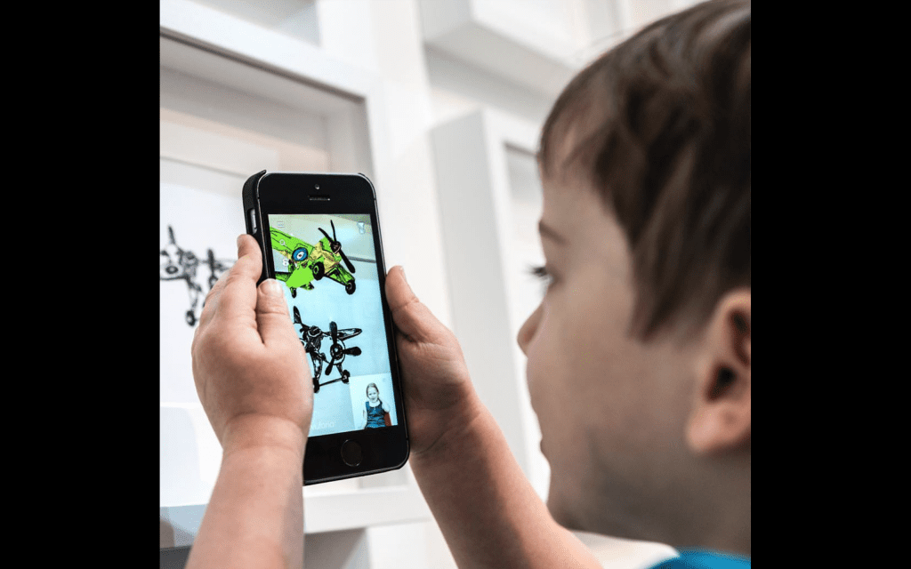 Child holding phone pointed at drawing which turns 3D on screen with someone demonstrating sign language.