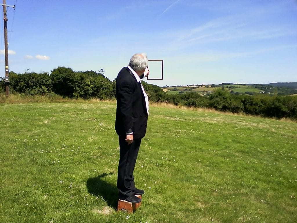 Man in suit stands in field holding up empty picture frame.