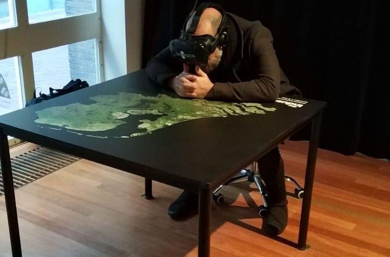 Man wearing VR headset looks at table of Netherlands with map on.