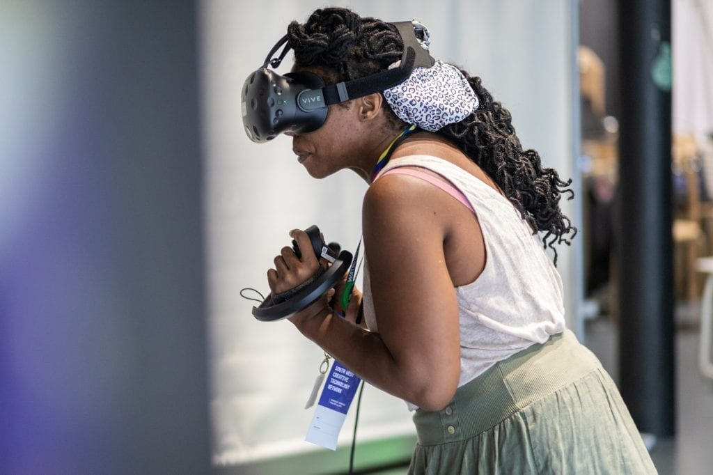 Woman wearing VR headset and holding remote at SWCTN Showcase.