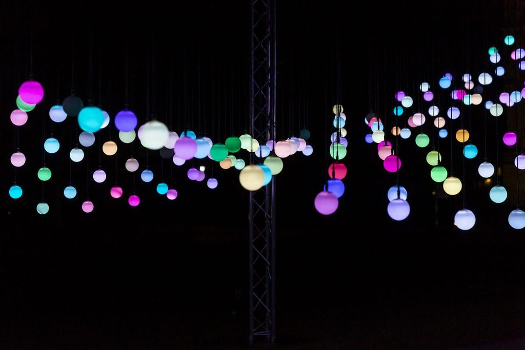 Strings of multicoloured lights hang from ceiling at AudioWave Squidsoup installation.