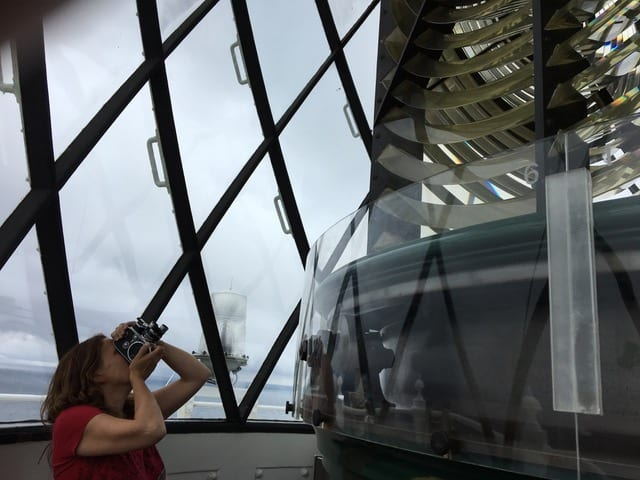 Woman uses camera to look up at object in front of her.