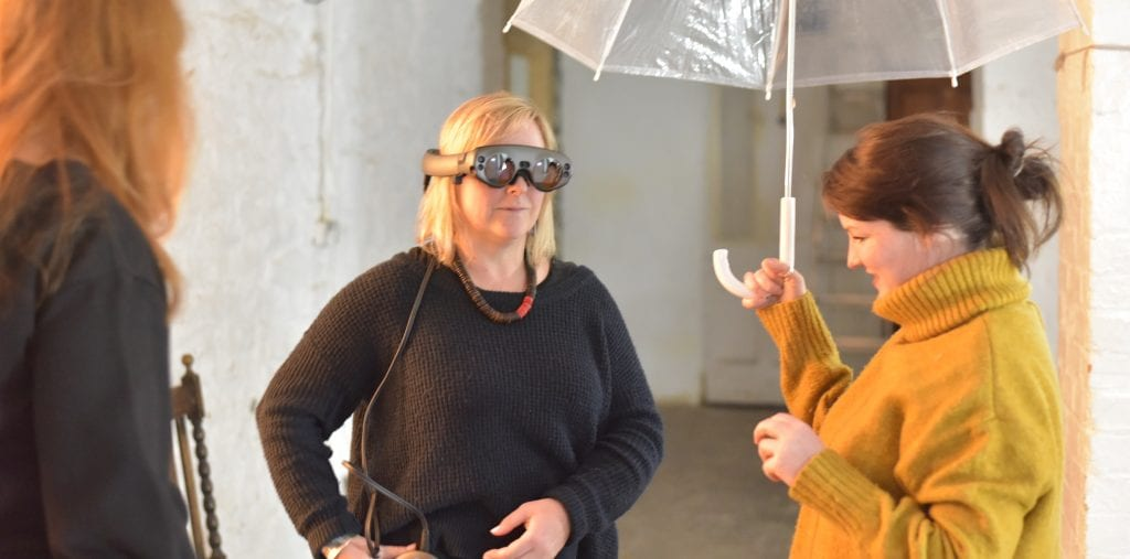 Woman in VR headset stands next to woman holding umbrella.