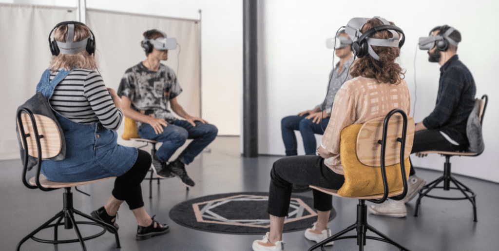 Group of 5 people sat on chairs in a circle wearing VR headsets.