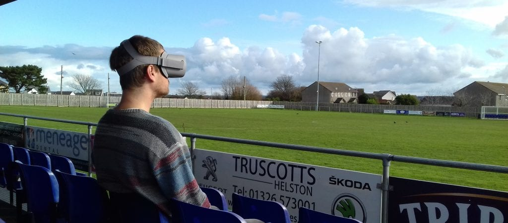Man in VR headset sits and looks at empty Helston AFC pitch.