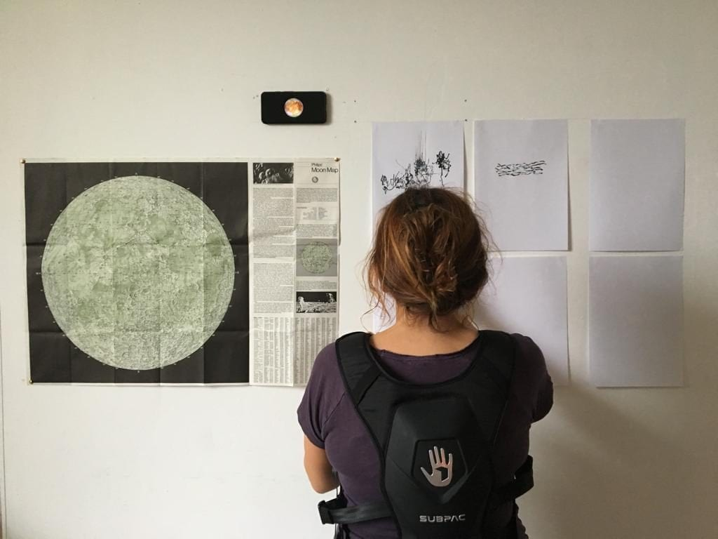 Woman looks at pieces of paper attached to wall.