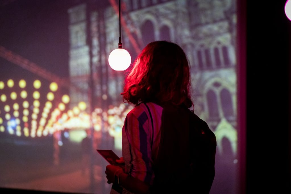 Person looks at pink glowing lightbulb in art installation.