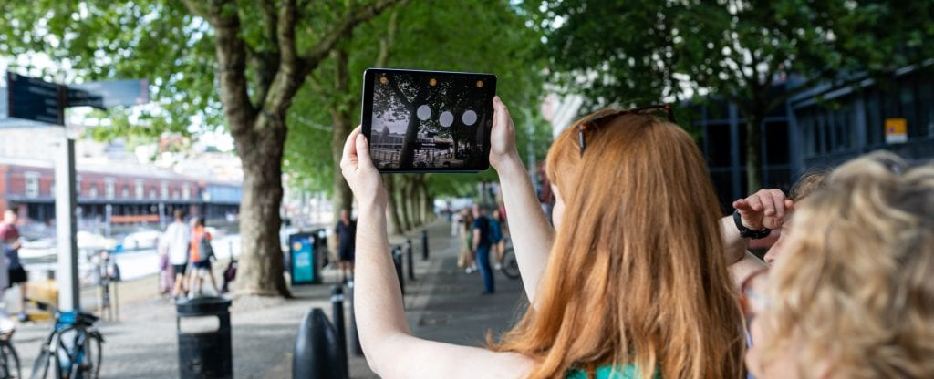 Woman holds tablet up to trees and screen shows information circles around image.