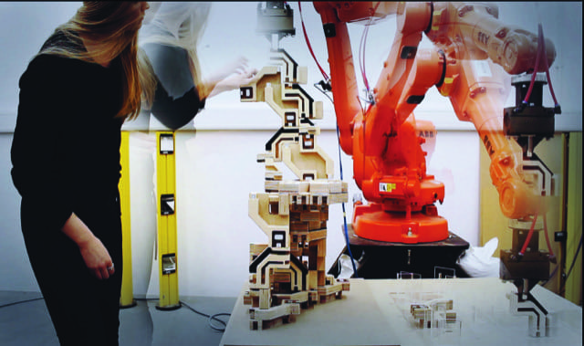 Woman works on machine with robotic arm in background.