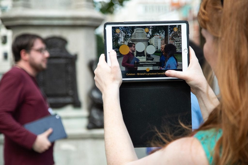 Woman holds tablet up to statue in front of her and it shows information about it.