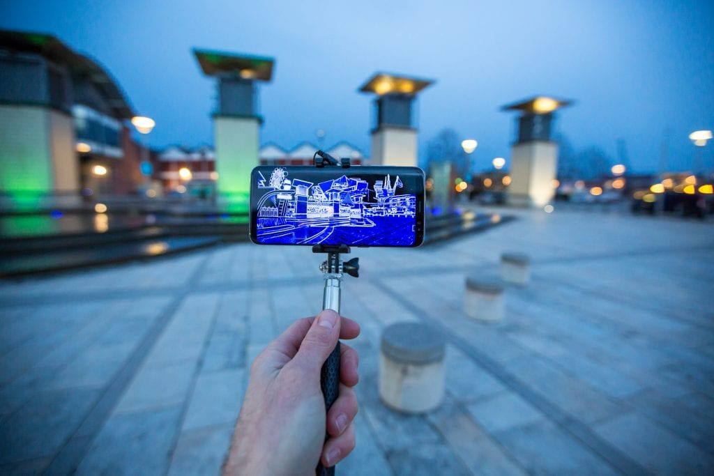 Hand holding selfie stick with phone in facing buildings and showing building plans on the screen.