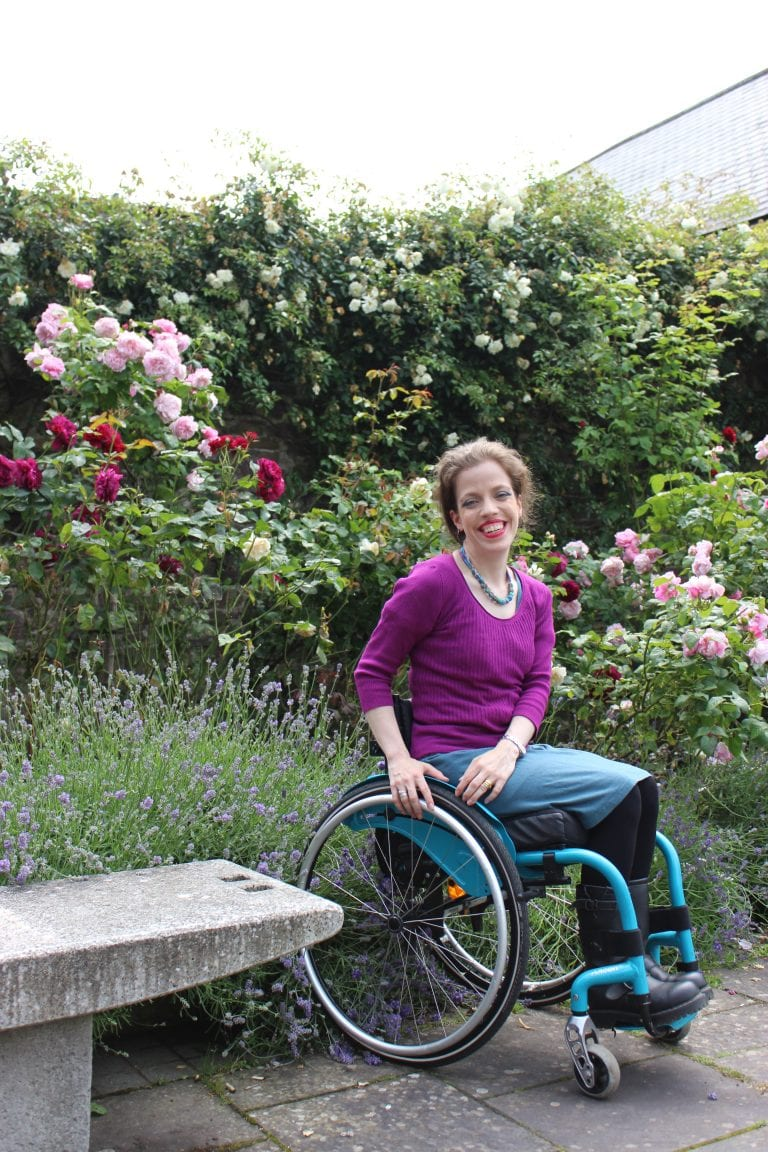 Grace Quantock sitting in front of a lavender bush, smiling in a wheelchair.