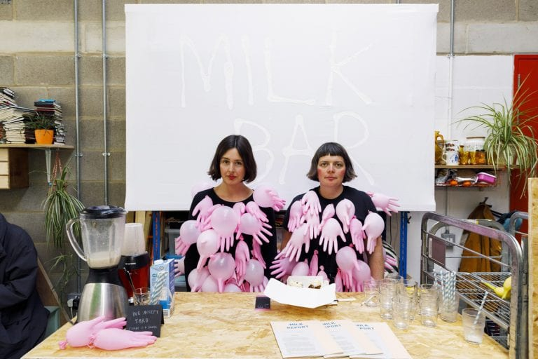Conway and Young wearing t-shirts with handshaped balloons attached, with the words 'Milk Bar' in the background.
