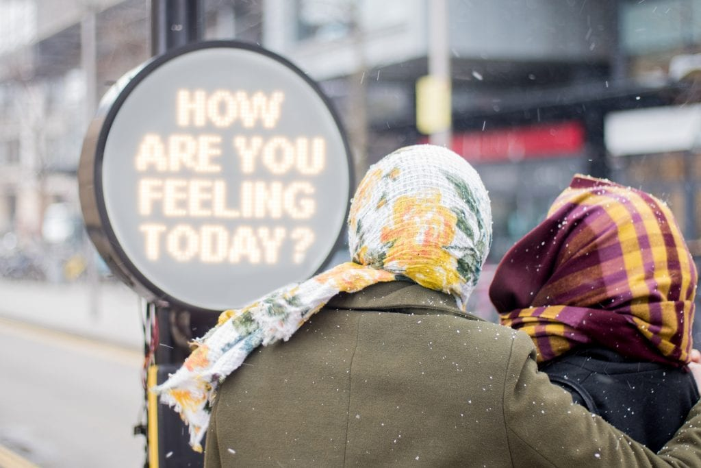 "The back of two people's heads wrapped in scarves reading a sign saying ""how are you feeling today?"""