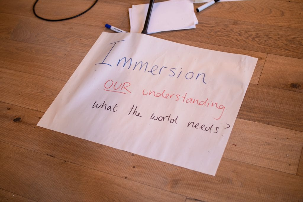 "Piece of paper with handwritten text saying ""Immersion our understanding what the world needs?"""
