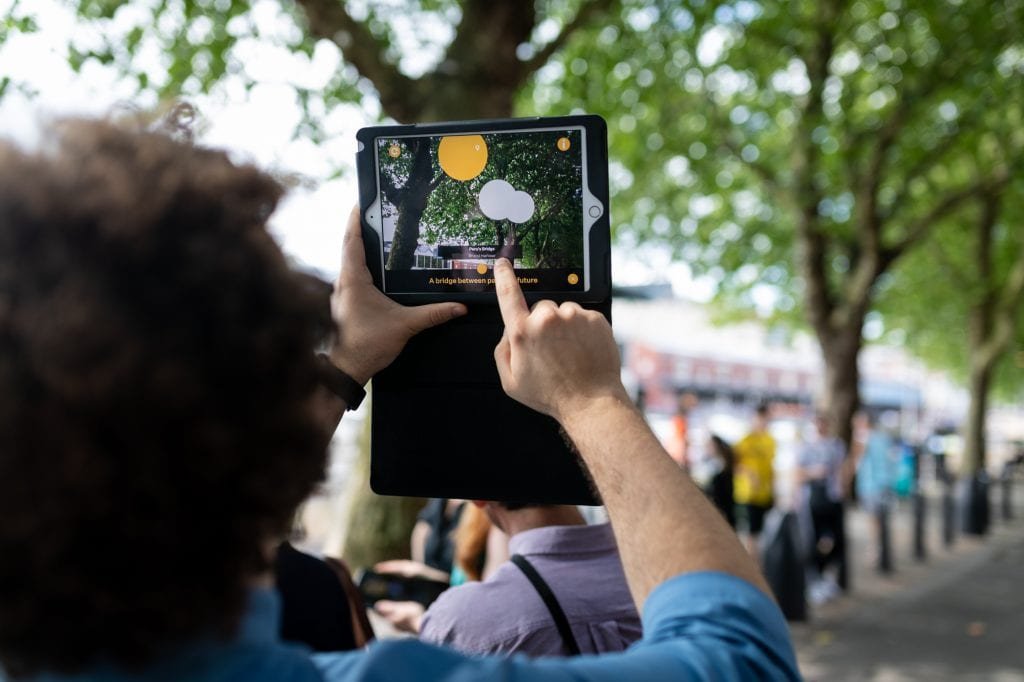Someone using tablet pointed towards trees, screen shows lights in front of trees.