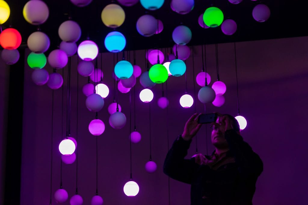 Man takes picture on phone of multicoloured light installation at Simple Things Festival 2019.