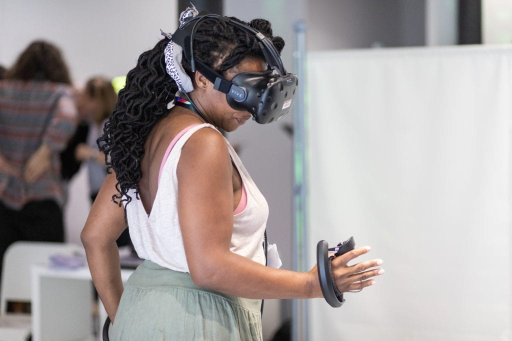 Woman stretches out her hand while wearing VR headset at SWCTN Showcase
