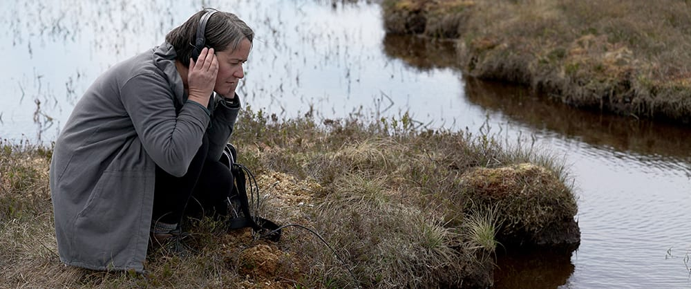 Photo of Kathy Hinde listening on headphones to a pond at a peat bog, which is a flat fast landscape with much water