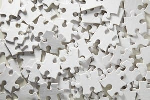 A jumbled pile of jigsaw puzzle pieces. All the pieces are blank and white making the puzzle almost impossible to complete.