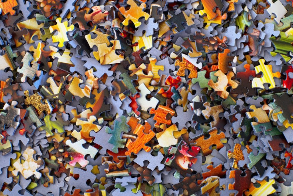 Pile of hundreds of loose, colourful jigsaw pieces