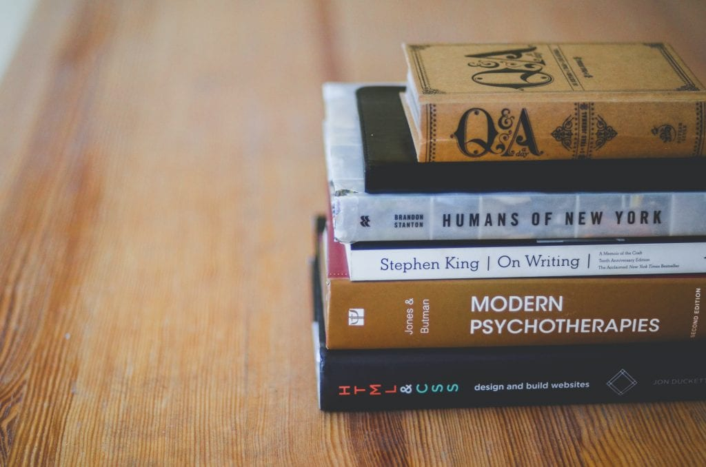 a stack of books on a wooden table