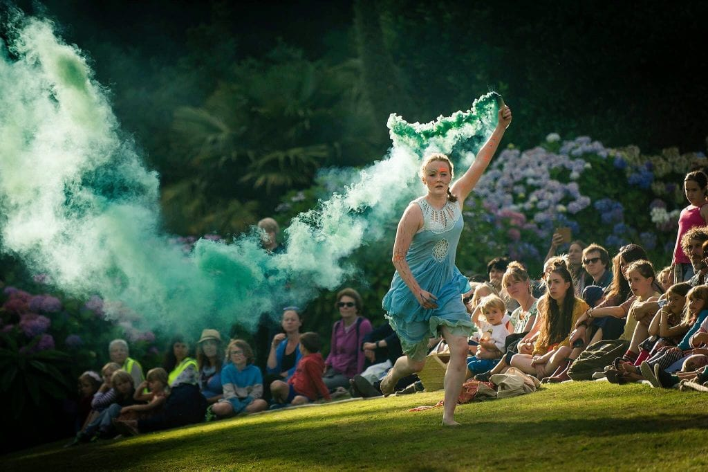image of a woman running on grass in a light blue dress, she is holding a canister that is releasing teal smoke as a sitting crowd watches