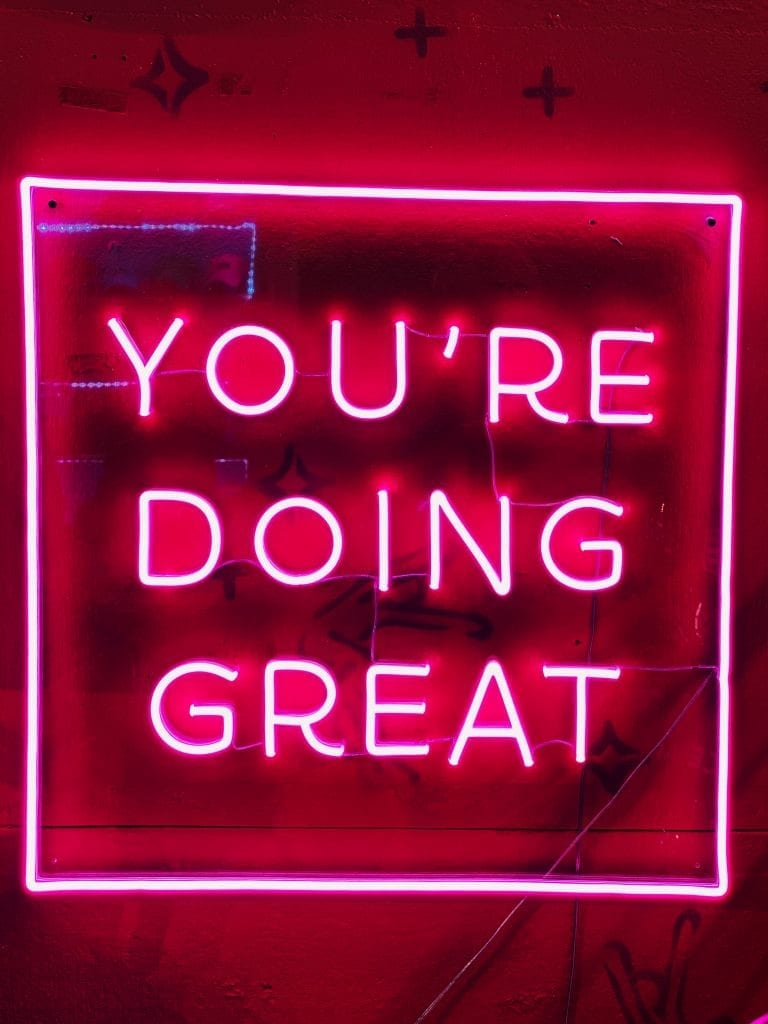 pink neon sign that reads; You're Doing Great