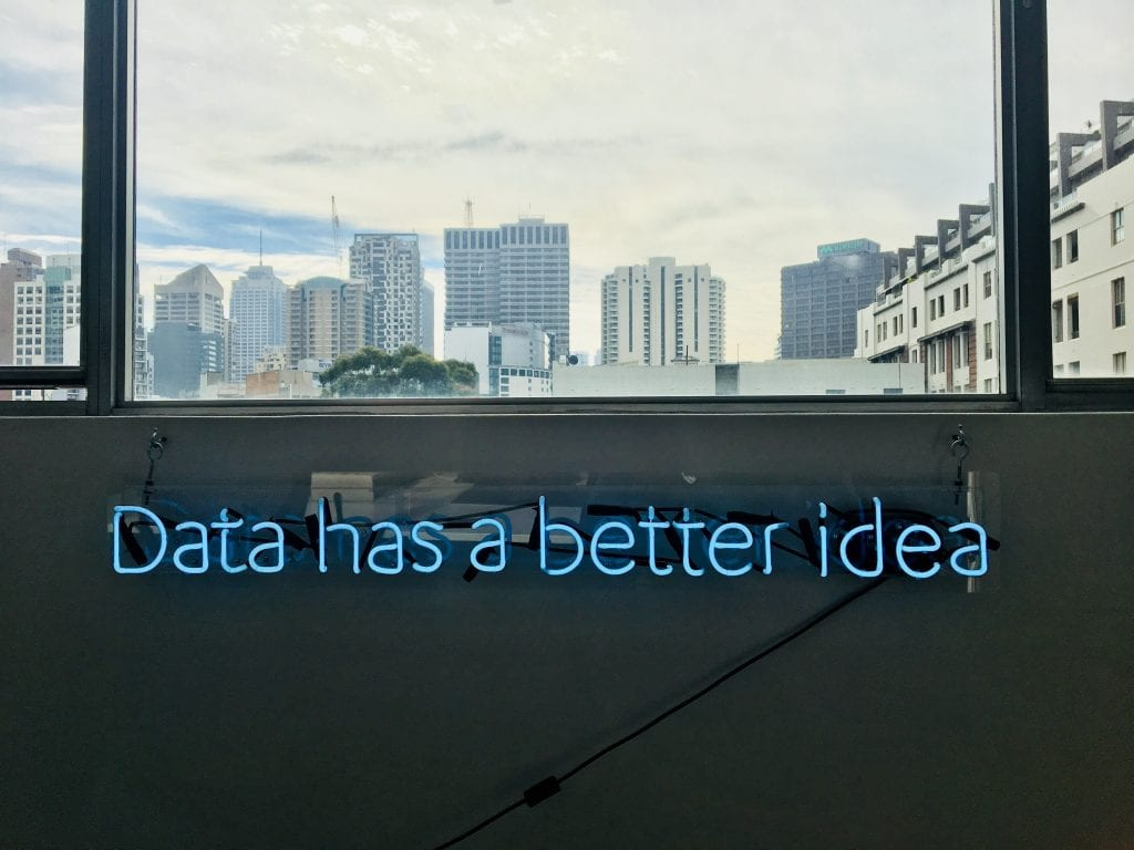 A blue neon sign hanging on the wall written 'data has a better idea'. Above is a widow view of a city landscape.