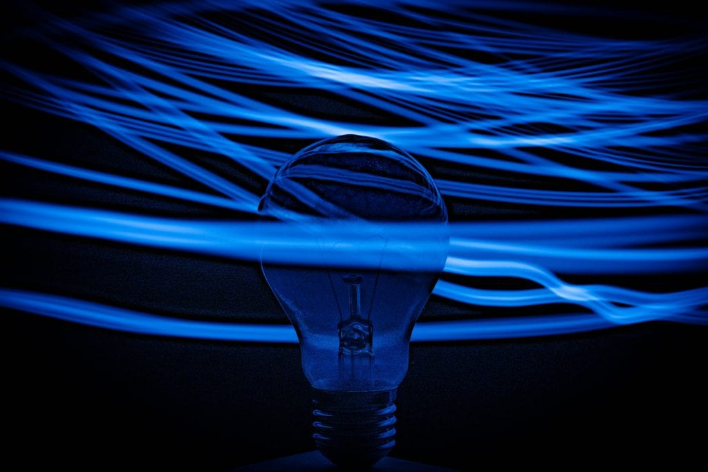 lightbulb surrounded by lines of light blue light. the background is dark blue